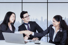 Workers closing a deal and shaking hands Stock Photos