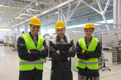 Workers in CNC factory. Team of three workers in CNC factory Stock Photo