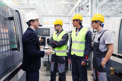 Workers at CNC plant. Manager and workers at plant near CNC machines Royalty Free Stock Images