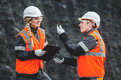 Workers with coal at open pit. Two speacialists examining coal at an open pit Stock Photo