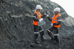 Workers with coal at open pit Royalty Free Stock Photo
