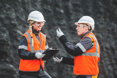 Workers with coal at open pit. Two speacialists examining coal at an open pit Stock Photos