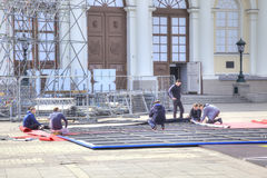 Workers collect a banner. MOSCOW, RUSSIA - April 24.2016: Brigade of workers collect enormous banner with a playbill to the future exhibition in Manege Royalty Free Stock Photo