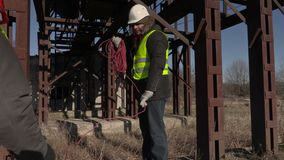 Workers collect power cord near metal tanks stock footage