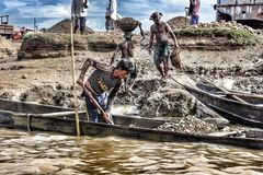 The workers are collecting stones from the boat. This place is situated in Bangladesh, Sylhet royalty free stock photography