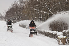 Workers of communal services remove the snow from the sidewalk with the help of motor vehicles Stock Photography