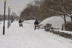 Workers of communal services remove the snow from the sidewalk with the help of motor vehicles Stock Image