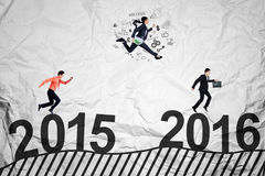 Workers compete above numbers 2016. Three entrepreneurs jumping and running above numbers 2015 to 2016 while compete to get success Royalty Free Stock Photos