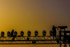 Workers on concert structure in the sunset backlight. Two workers are dismounting the irony structure that holds the lights, during the sunset. Backlight image Royalty Free Stock Photos