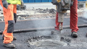 Workers with Concrete Breaker - pneumatic hammer. Sofia, Bulgaria - 23 August 2017: Worker with Concrete Breaker - air hammer repairs the hot asphalt on a street stock footage
