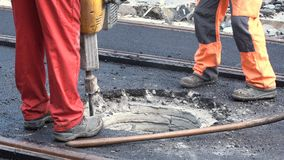 Workers with concrete breaker - pneumatic hammer. Worker with concrete breaker - air hammer repairs the hot asphalt on a street along tram car`s railroad lines stock video footage