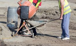 Workers with concrete mixer. Construction workers pouring fresh concrete from electrical mixer into wheelbarrow at building site Stock Photos