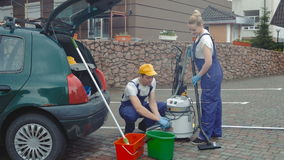 The workers connect a vacuum cleaner. Cleaning lady keeps brush from the vacuum cleaner in hand. Cleaner connects with a vacuum cleaner hose. Cleaners connect stock footage