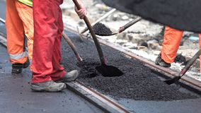 Workers construct asphalt road and railroad lines. Team of workers put the hot asphalt on a street along tram car`s railroad lines. Road construction workers stock footage