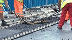 Workers construct asphalt road and railroad lines. Team of workers put the hot asphalt on a street along tram car`s railroad lines. Road construction workers stock video footage
