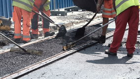 Workers construct asphalt road and railroad lines. Team of workers put the hot asphalt on a street along tram car`s railroad lines. Road construction workers stock video
