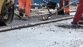 Workers construct asphalt road and railroad lines. Team of workers put the hot asphalt on a street along tram car`s railroad lines. Small steamroller. Road stock video