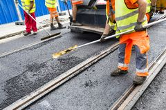 Workers construct asphalt road and railroad lines royalty free stock photos