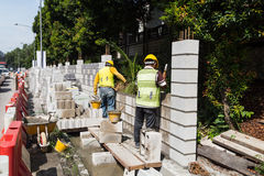 Workers constructing building noise barrier walls at busy highway royalty free stock image