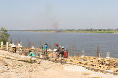The workers are constructing the pier beside Mekong river near t Royalty Free Stock Photos