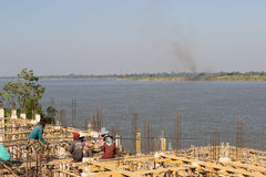 The workers are constructing the pier beside Mekong river near t Royalty Free Stock Photo