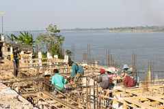 The workers are constructing the pier beside Mekong river near t Royalty Free Stock Image
