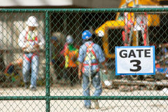 Workers in construction site, focus on chain link fence. Royalty Free Stock Images