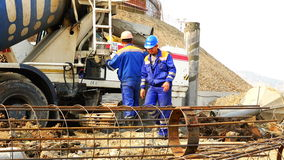 Workers at the construction site receive concrete from a concrete mixer and poured into a casing into a casing stock video footage