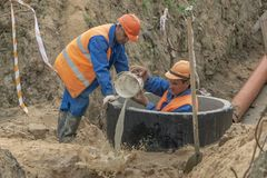 Workers at the construction site scoop water out of the well royalty free stock photos