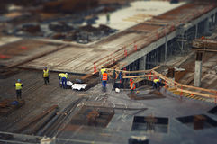 Workers at the construction site. Tilt-shif lens Royalty Free Stock Photos