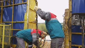 Workers control pipe lifting by oil exploratory drilling machine under cloudy