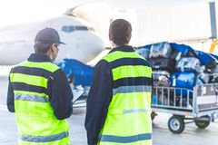 Workers controlling luggage in airdrome Royalty Free Stock Photography