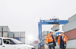 Workers conversing while walking in shipping yard Stock Photo