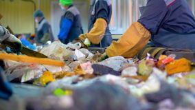 Workers at conveyor sorting garbage at a recycling plant. 4K stock footage