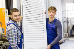 Workers in coverall with  PVC window with shutter Stock Image