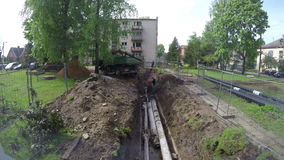 Workers and crane remove old heating tube in small city street. PANEVEZYS DISTRICT, LITHUANIA -  May, 2015: workers and crane remove old heating tube in small stock footage