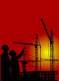 Workers and cranes at sunset Royalty Free Stock Photo