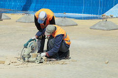 Workers cut concrete paving Stock Image