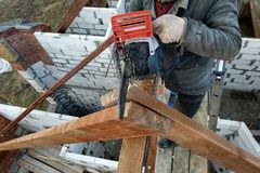 Workers cut the rafters on the roof of the chainsaw house royalty free stock photo