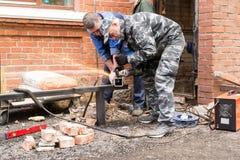 Workers Cutting Metal Tubing Stock Photo