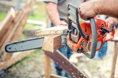 Workers cutting timber wood with chainsaw. Men sawing using electrical chainsaw Stock Photo