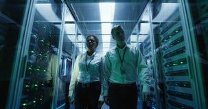 Workers in a data center walking between rows of server racks