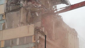 Workers demolishing a house with machinery. Day shot of an excavator demolishing a house using a hydraulic scissors stock footage