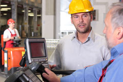Workers discussing. A young worker discussing with a senior worker operating a device stock photography