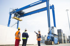Workers discussing against large crane loading container at shipping yard Royalty Free Stock Images