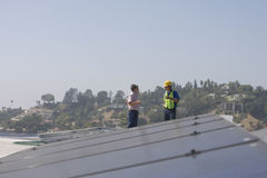 Workers Discussing Near Solar Panels Stock Photo