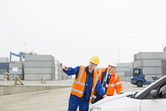 Workers discussing over blueprint in shipping yard Royalty Free Stock Photos