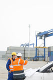 Workers discussing over blueprint in shipping yard Royalty Free Stock Photo