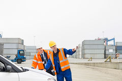 Workers discussing over blueprint in shipping yard Stock Image