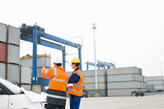 Workers discussing over blueprint in shipping yard Royalty Free Stock Photography